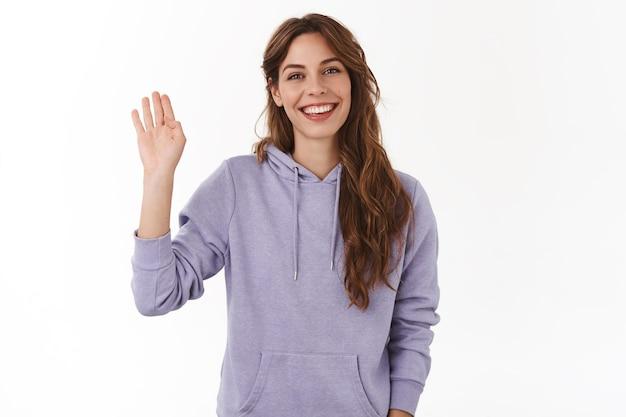 Vrolijke charismatische aantrekkelijke vriendelijke vrouw zwaaien opgeheven hand hallo groet gebaar glimlachend brede perfecte grijns introduceert zichzelf nieuwe mensen ontmoeten verwelkomende gasten, witte muur