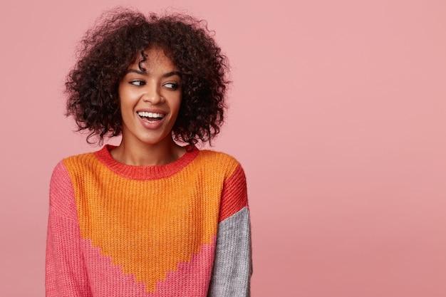 Vrolijke charismatische afro-amerikaanse vrouw met een afro kapsel met opwinding kijkt links naar de lege ruimte, lacht, ha-ha, met kleurrijke trui, geïsoleerd op roze