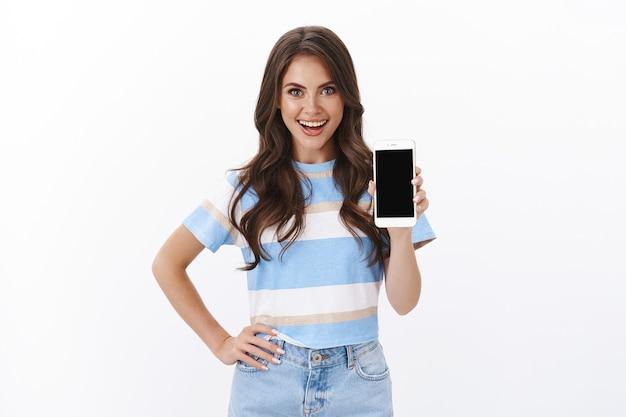 Vrolijke charismatische europese vrouw introduceert smartphonefunctie, raad app aan, glimlach tevreden en brutaal, houd hand op taille zelfverzekerd en brutale pose, toon mobiele telefoonscherm