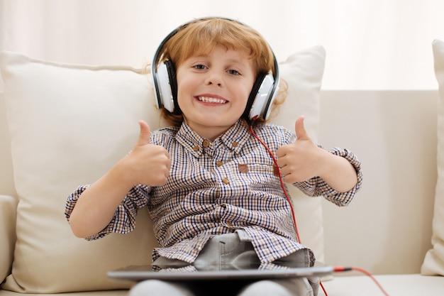 Vrolijke charismatische knappe jongen die zijn vrije tijd thuis doorbrengt en geniet van videogames terwijl hij zijn tablet gebruikt en een koptelefoon draagt