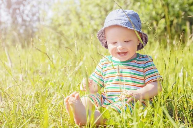 Vrolijke charmante baby in panamahoed zit op de weide op zonnige zomerdag, zomertijd, kinderdag