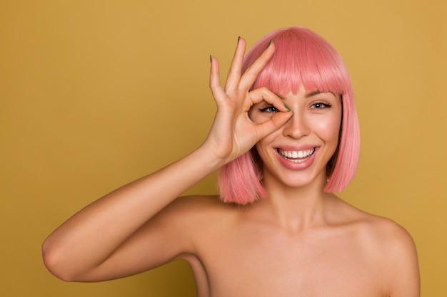 Vrolijke charmante jonge blauwogige rozeharige vrouw met bob kapsel die in een hoge geest is en gelukkig lacht terwijl ze over de mosterdmuur staat met opgeheven ok teken