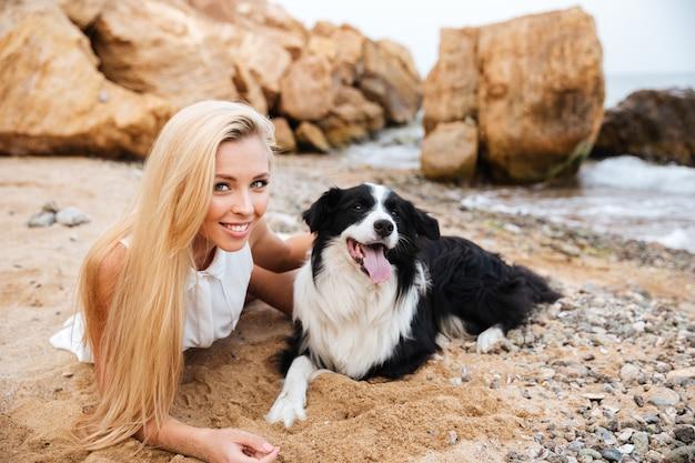 Vrolijke charmante jonge vrouw die ligt en haar hond knuffelt op het strand