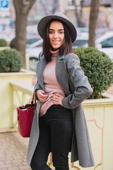 Vrolijke charmante jonge vrouw met donkerbruin haar in lange grijze vacht, hoed lopen op straat in stadspark. elegante vooruitzichten, luxe levensstijl, modieus model, glimlachend.