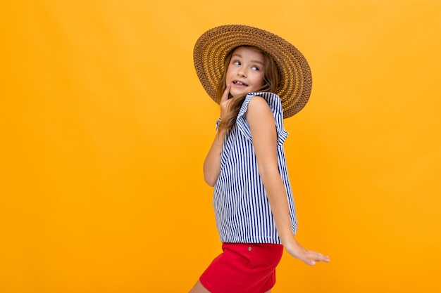 Vrolijke charmante meisje in een zomer stro hoed op fel oranje