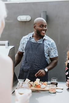 Vrolijke chef-kok die barbecueleerpennen roosteren bij een dakpartij