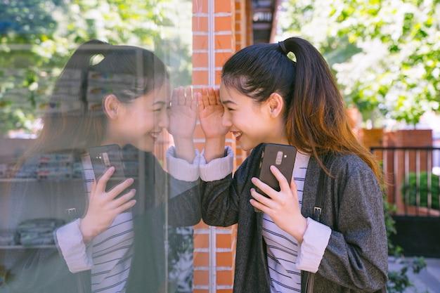 Vrolijke chinese vrouw die aan een etalage kijkt en met de telefoon met vrienden spreekt.
