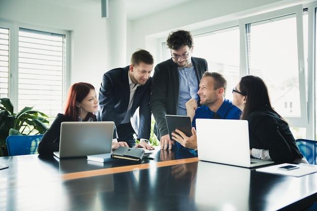 Vrolijke collega's aan tafel met gadgets
