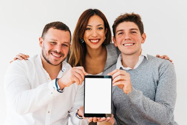 Vrolijke collega's die nieuwe tablet voorstellen
