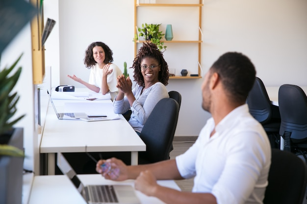 Vrolijke collega's die op het werk communiceren