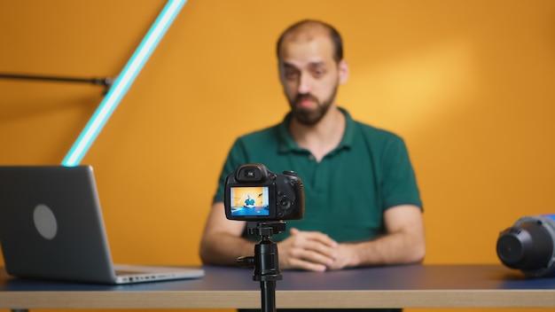 Vrolijke contentmaker zwaait tijdens het opnemen van podcast in thuisstudio. podcast en recensie van sociale media, bloggen, vloggen, digitaal internetwebtijdperk, influencer-opname voor online distributie
