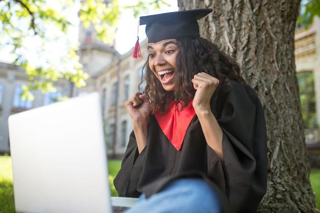 Vrolijke dag. een schattige afgestudeerde in academische toga die een videogesprek heeft en zich gelukkig voelt