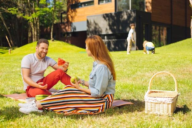 Vrolijke dag. geïnspireerd bebaarde man watermeloen te houden en te praten met zijn vrouw