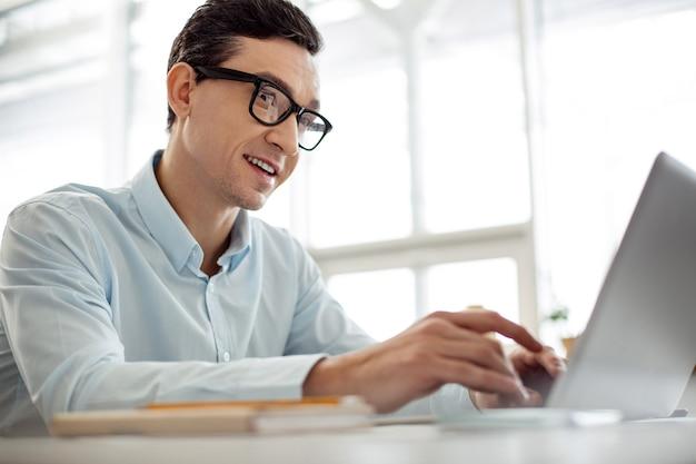 Vrolijke dag. knappe inhoud donkerharige man die lacht en werkt op zijn laptop en een bril draagt terwijl hij aan tafel zit