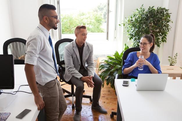 Vrolijke dame baas praten met werknemers