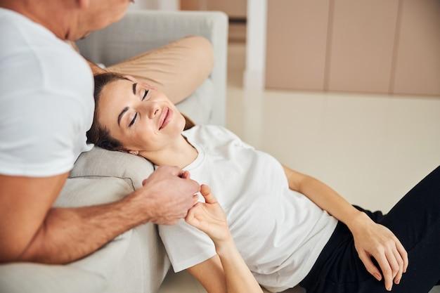 Vrolijke dame die in de buurt van haar geliefde man slaapt