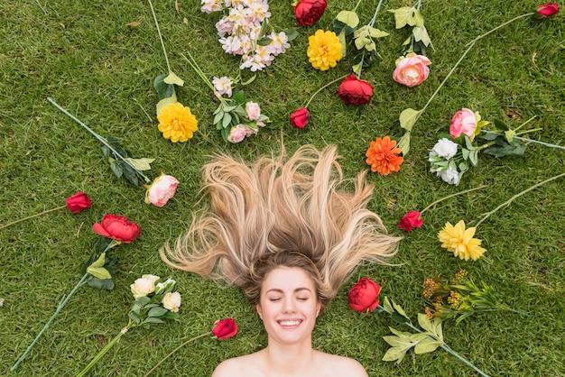 Vrolijke dame die op gras tussen bloemen ligt