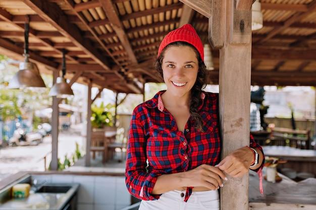 Vrolijke dame die zich voordeed op de camera op de achtergrond van hout open ruimte café. vrouwelijke toerist heeft plezier op zonnige zomerdag. concept van enkele reisvakanties en geluk