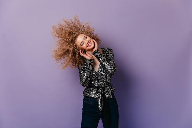 Vrolijke dame gekleed in zwart jasje met zilveren glitters en spijkerbroek die krullend blond haar op geïsoleerde ruimte speelt.