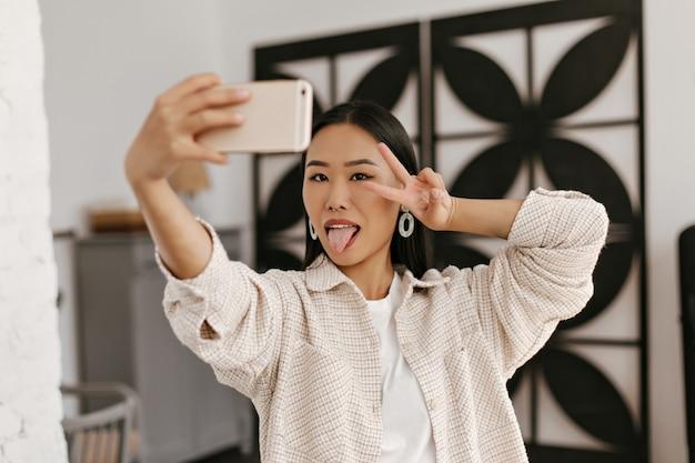 Vrolijke dame in beige jasje toont v-teken en neemt selfie op keuken