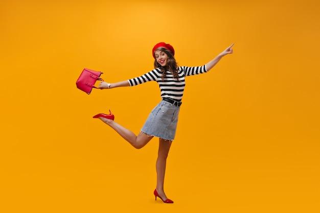 Vrolijke dame in gestreept overhemd, rode baret jumping. n oranje achtergrond. ith handtas. aantrekkelijke jonge vrouw in baret en trendy schoenen poseren.