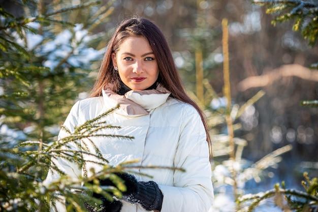 Vrolijke dame in winterkleren poseren met vreugde buiten in het sneeuwbos