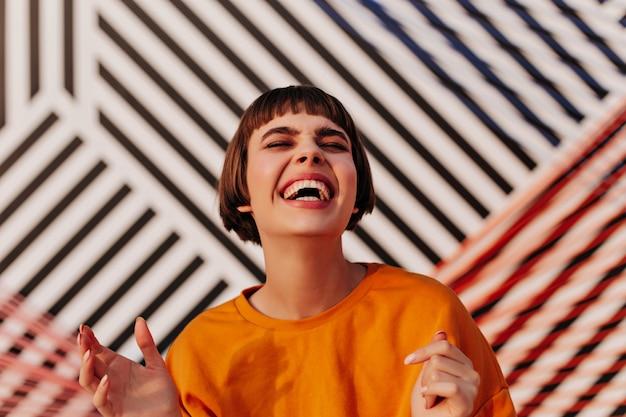 Vrolijke dame met donkerbruin kapsel in oranje sweatshirt die buiten lacht