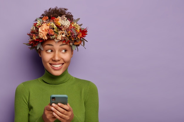Vrolijke dame met donkere huid, brede glimlach, mooie krans gemaakt van herfstplanten, berichten via mobiele telefoon, kijkt opzij met blije uitdrukking