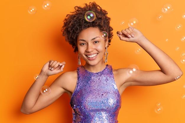 Vrolijke dame met krullend kapsel dansen op feestje schudt armen glimlacht gelukkig heeft goed humeur gekleed in glinsterende paarse t-shirt geïsoleerd over oranje muur zeepbellen rond geniet goede dag