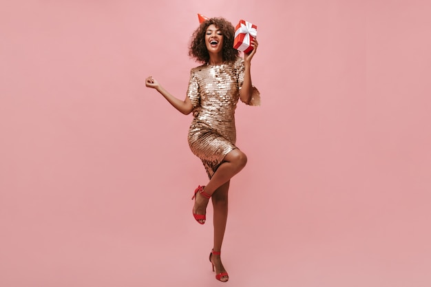 Vrolijke dame met krullend kapsel in beige glanzende jurk, coole schoenen en vakantiepet die zich verheugt en rode geschenkdoos op roze muur houdt..