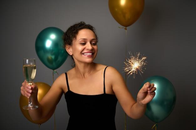 Vrolijke dame van gemengd ras heeft plezier op jubileumfeest, kerstmis, nieuwjaarsevenement. mooie vrouw houdt glas mousserende wijn en wonderkaarsen vast. grijze achtergrond met gouden en groene luchtballonnen