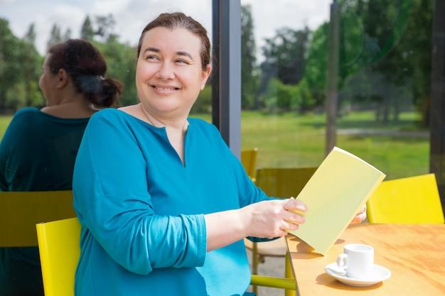 Vrolijke dame van middelbare leeftijd die haar ochtend in coffeeshop doorbrengt