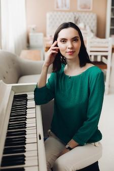 Vrolijke dame zit op de stoel in de buurt van de witte piano
