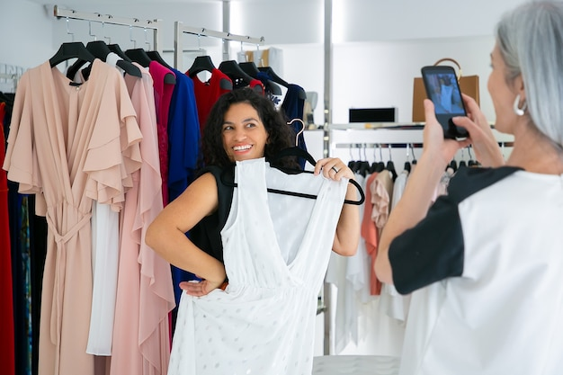 Vrolijke dames die genieten van het samen winkelen in een boetiek, een jurk vasthouden, plezier hebben en foto's maken op de mobiele telefoon. consumentisme of winkelconcept