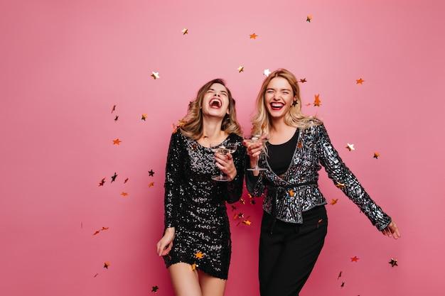Vrolijke dames die iets vieren. vrouwelijke modellen in fonkelingsjurken die op roze muur dansen.