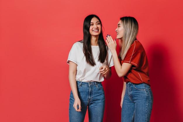 Vrolijke dames in goed humeur chatten op rode muur