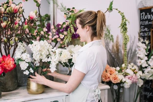 Vrolijke die vrouw met bloemen het samenstellen wordt opgewekt