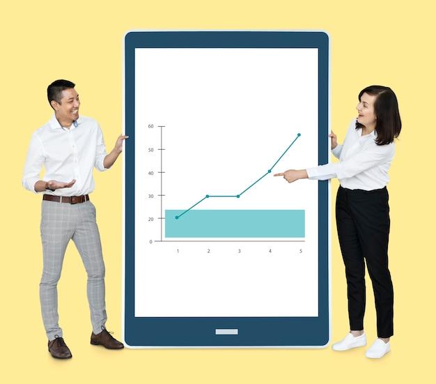 Vrolijke diverse mensen die een grafiek op een tablet tonen
