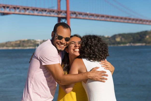 Vrolijke diverse vrienden knuffelen in de buurt van de rivier