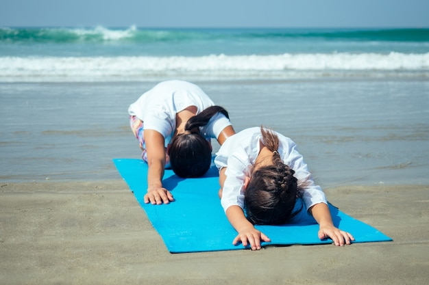 Vrolijke dochter en moeder die yoga doen op het strand