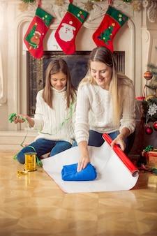 Vrolijke dochter en moeder wikkelen trui in inpakpapier op kerstavond