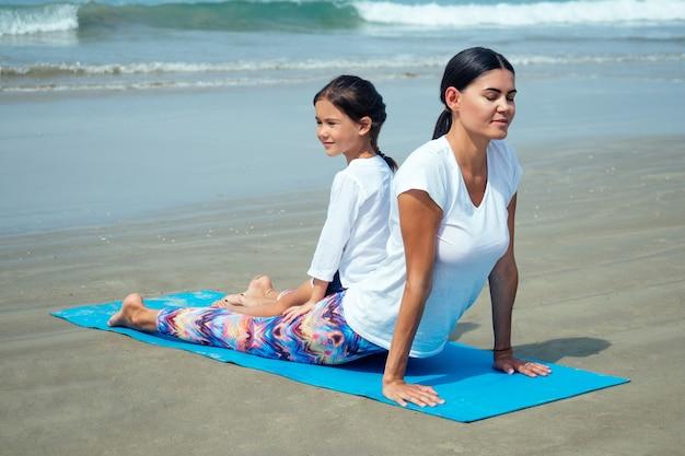 Vrolijke dochter en mooie moeder die yoga beoefent op het strand