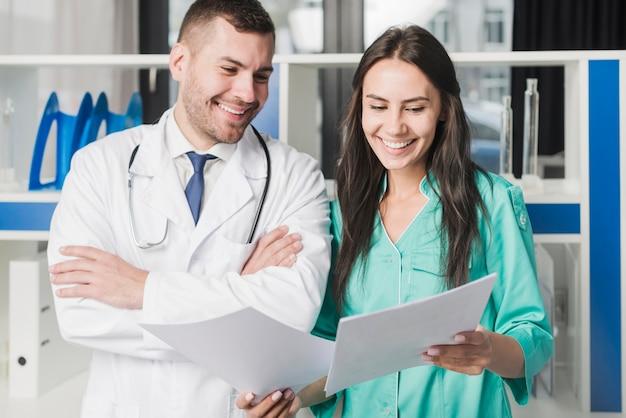 Vrolijke dokters staan met papier