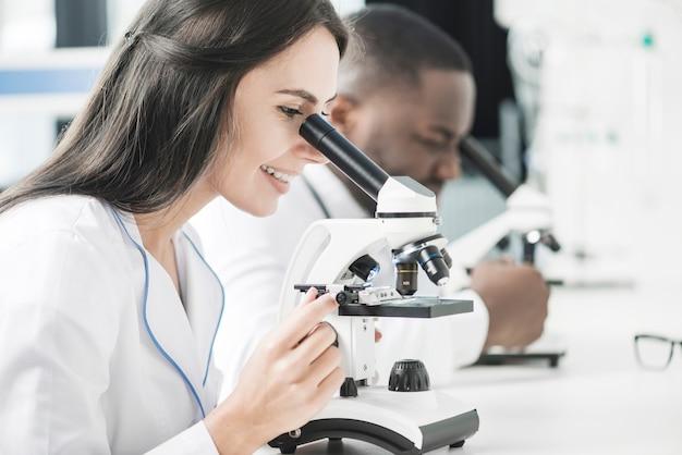 Vrolijke doktersvrouw die microscoop bekijkt