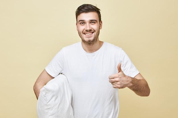 Vrolijke dolblij jonge blanke man in wit t-shirt met stralende glimlach, ontspannen en enegetisch gevoel na een goede diepe slaap op nieuw kussen, duimen opdagen