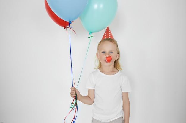 Vrolijke dolblij schooljongen met blond haar dragen vakantie kegel hoed en wit t-shirt poseren op witte lege muur, blauwe en rode ballonnen vasthouden, fluitje blazen, plezier op verjaardagsfeestje