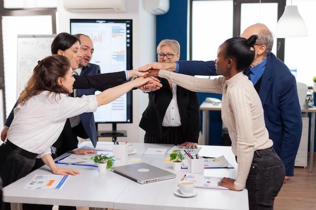 Vrolijke dolblije zakenmensen in vergaderruimte die aan het celebreren zijn diverse collega's met nieuwe kans om te genieten van een overwinningsvergadering in een kamerkantoor