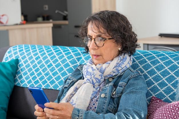 Vrolijke donkerbruine hogere vrouw die smartphone gebruiken terwijl het zitten op bank