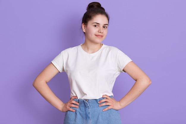 Vrolijke donkerbruine tiener met haarbroodje het stellen tegen lilac muur
