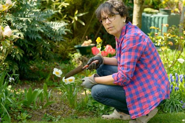 Vrolijke donkerbruine vrouw die bloemen in tuin planten